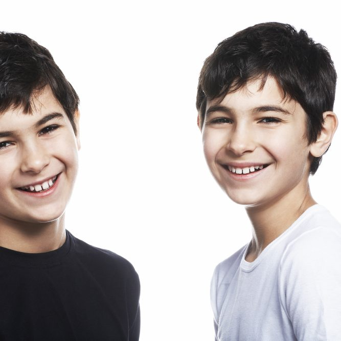 Twin boys (13-15) smiling, portrait